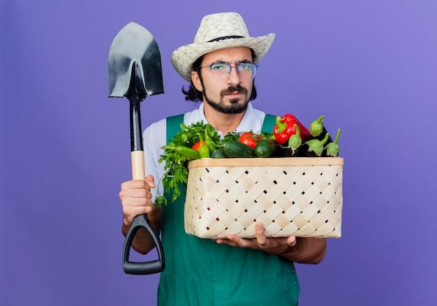 Homem jovem jardineiro barbudo vestindo macacão e chapéu segurando uma caixa cheia de legumes e uma pá olhando para frente com uma cara séria em pé sobre a parede azul