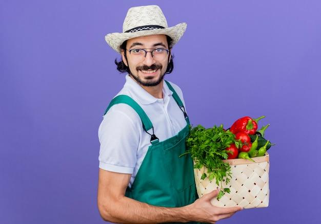 Homem jovem jardineiro barbudo vestindo macacão e chapéu segurando uma caixa cheia de vegetais olhando para a frente sorrindo alegremente em pé sobre a parede azul