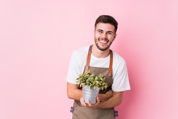 Homem jovem jardineiro caucasiano segurando uma planta isolada rindo e se divertindo.