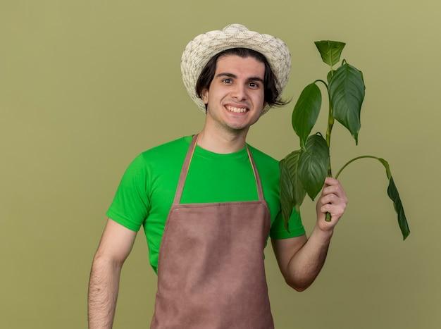 Homem jovem jardineiro satisfeito de avental e chapéu segurando uma planta olhando para a câmera com um sorriso no rosto em pé sobre um fundo claro