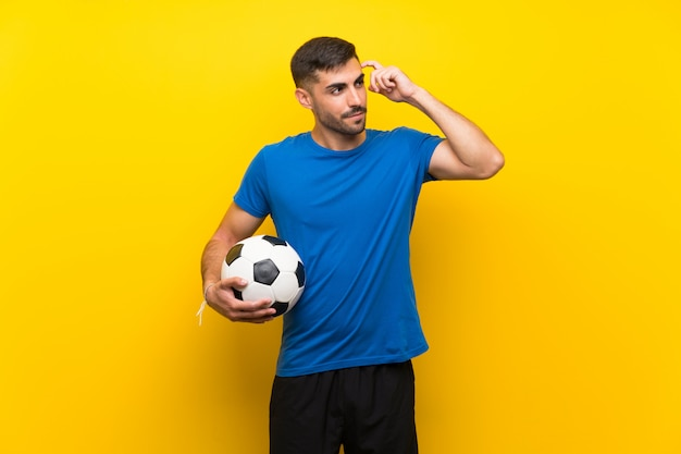 Homem jovem jogador de futebol com dúvidas e com expressão confusa