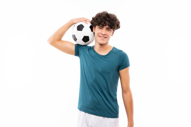Homem jovem jogador de futebol sobre parede branca isolada