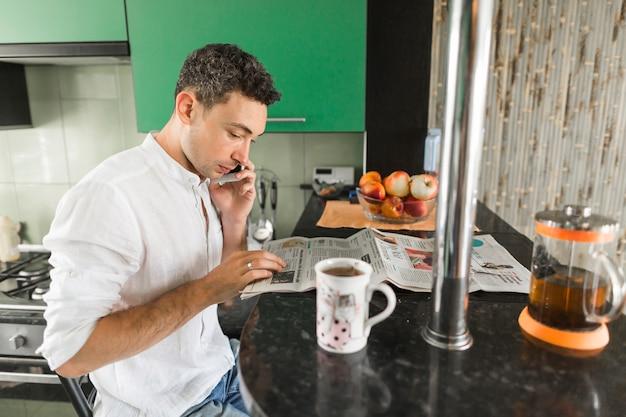 Homem jovem, jornal leitura, falar telefone móvel, em, contador cozinha