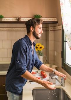 Homem jovem, lavando, rabanete branco, em, pia