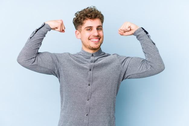 Homem jovem loiro cabelo encaracolado, mostrando o gesto de força com os braços