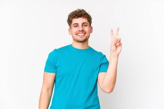 Homem jovem loiro encaracolado caucasiano isolado alegre e despreocupado, mostrando um símbolo de paz com os dedos.