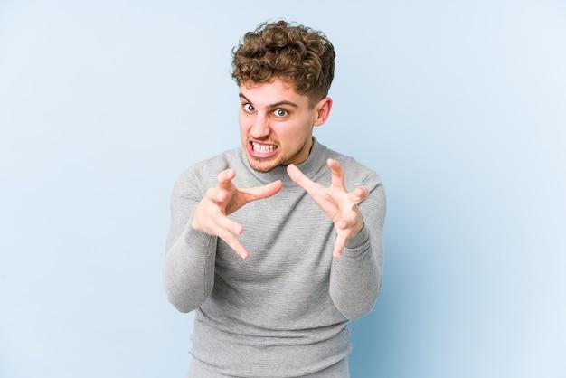 Homem jovem loiro encaracolado caucasiano isolado chateado gritando com as mãos tensas.