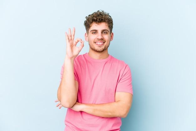 Homem jovem loiro encaracolado caucasiano isolado pisca um olho e segura um gesto de ok com a mão.