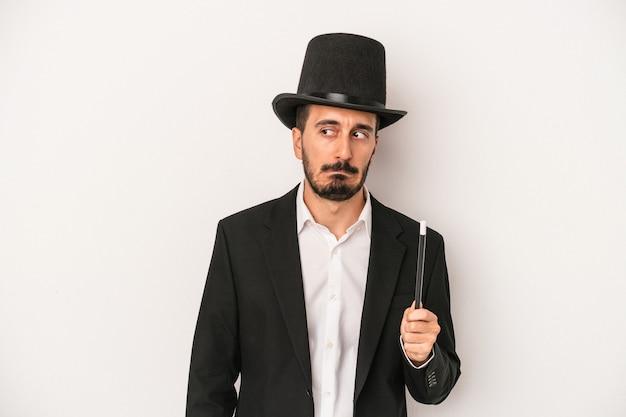 Homem jovem mágico segurando a varinha isolada no fundo branco confuso, sente-se em dúvida e inseguro.