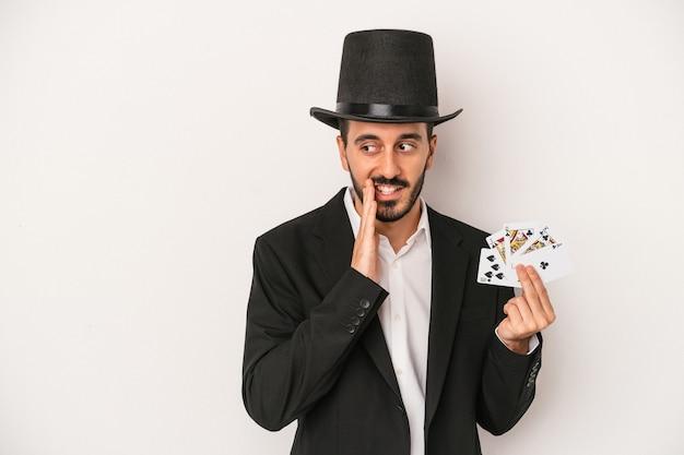 Homem jovem mágico segurando um cartão mágico isolado no fundo branco está contando uma notícia secreta de travagem e olhando para o lado