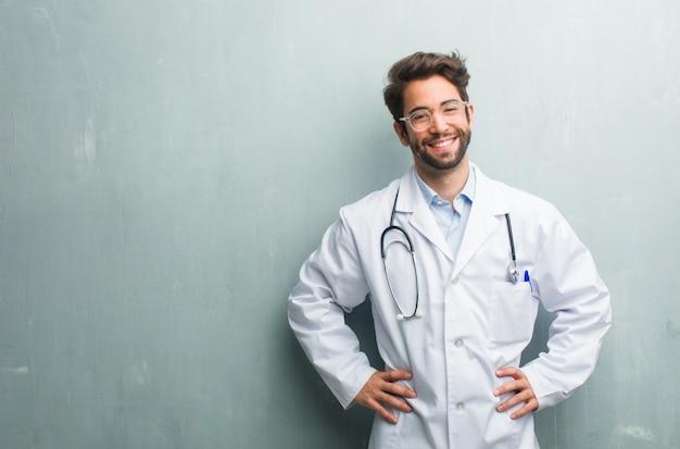 Homem jovem médico amigável contra uma parede de grunge com um espaço de cópia com as mãos nos quadris, stan