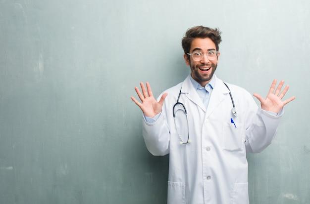 Homem jovem médico amigável contra uma parede de grunge com um espaço de cópia gritando feliz