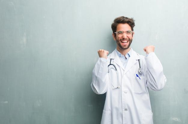Homem jovem médico amigável contra uma parede de grunge com um espaço de cópia muito feliz e animado