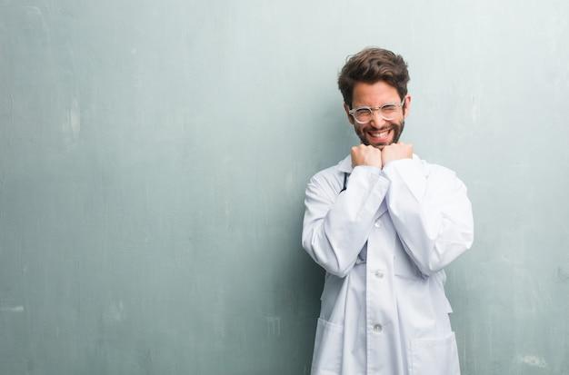 Homem jovem médico amigável contra uma parede de grunge com um espaço de cópia muito feliz e excitet
