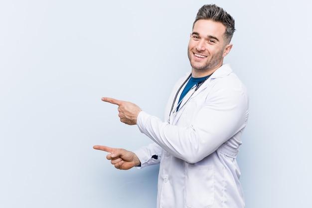 Homem jovem médico bonito animado apontando com o dedo indicador fora.