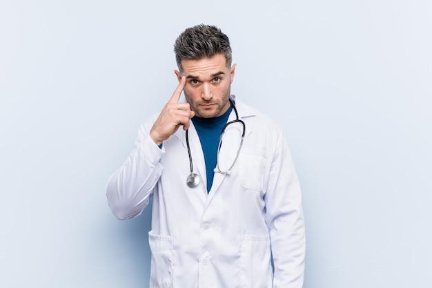 Homem jovem médico bonito apontando o templo com o dedo, pensando, focado em uma tarefa.