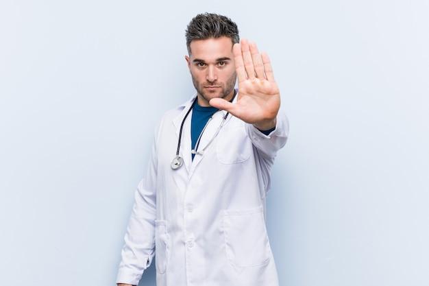 Homem jovem médico bonito em pé com a mão estendida, mostrando o sinal de stop