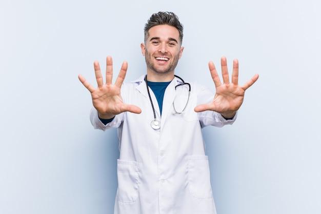 Homem jovem médico bonito mostrando o número dez com as mãos.