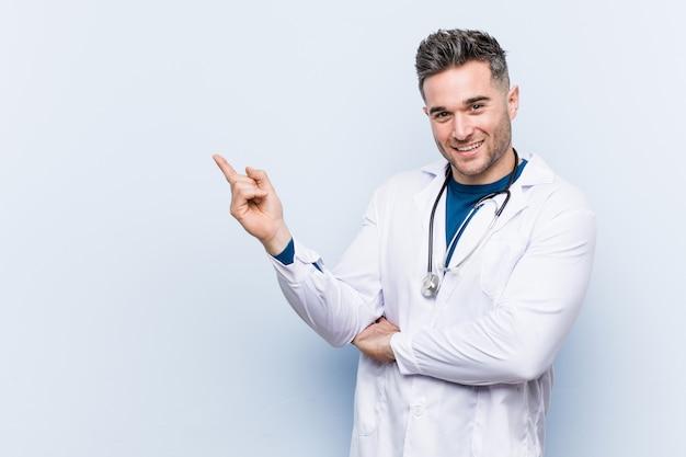Homem jovem médico bonito sorrindo alegremente apontando com o dedo indicador fora.