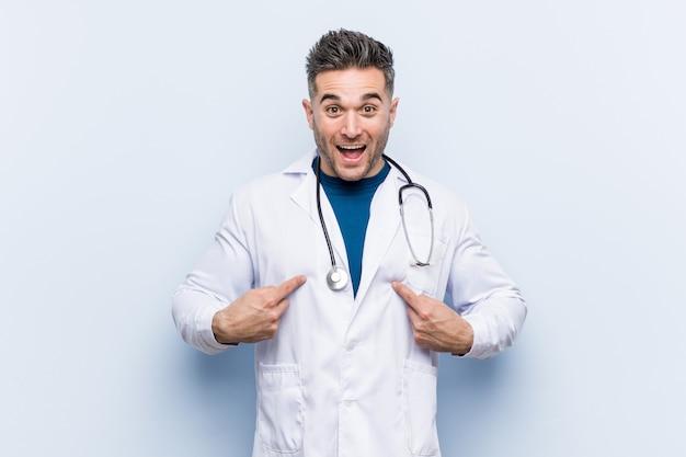 Homem jovem médico bonito surpreendeu apontando com o dedo, sorrindo amplamente.