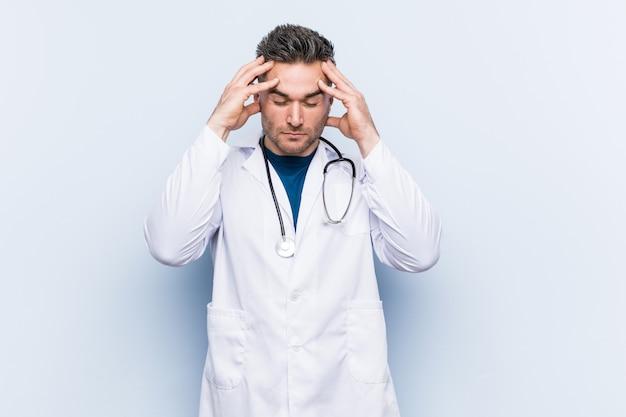 Homem jovem médico bonito tocando os templos e tendo dor de cabeça.