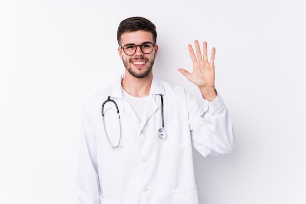 Homem jovem médico caucasiano isolado sorrindo alegre mostrando o número cinco com os dedos.