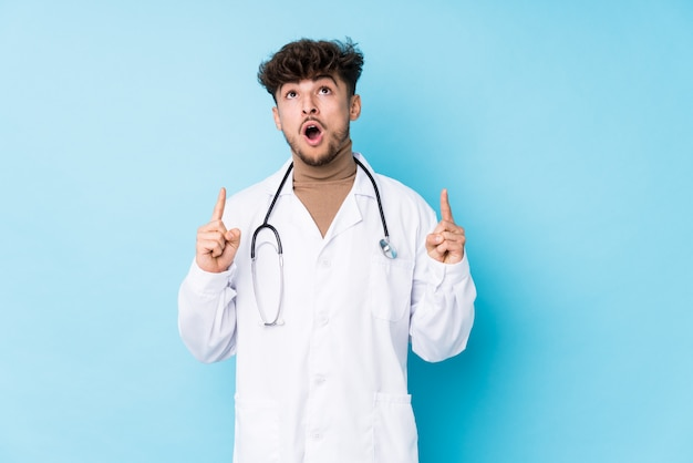 Homem jovem médico idolatrado apontando de cabeça com a boca aberta.