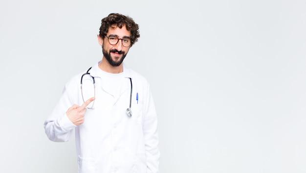 Homem jovem médico olhando orgulhoso, confiante e feliz, sorrindo e apontando para si mesmo ou fazendo o sinal número um contra a parede do espaço de cópia