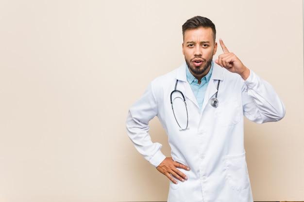 Homem jovem médico sul-asiático, tendo uma idéia, conceito de inspiração.