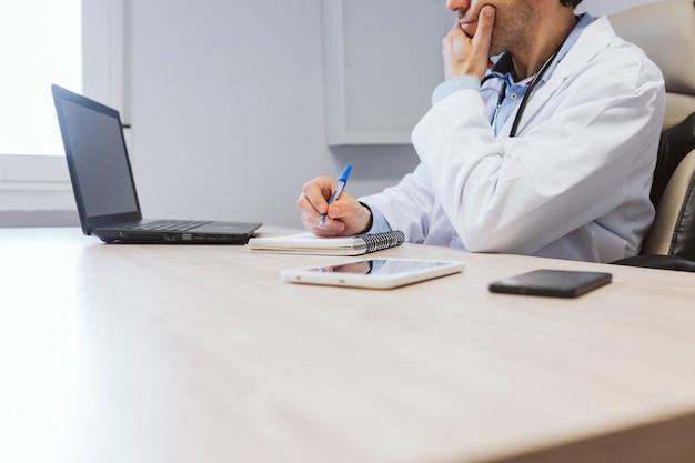Homem jovem médico trabalhando no laptop na consulta. conceito médico moderno dentro de casa