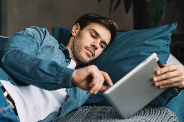 Homem jovem, mentindo lado, sobre, a, cama, olhar, tablete digital