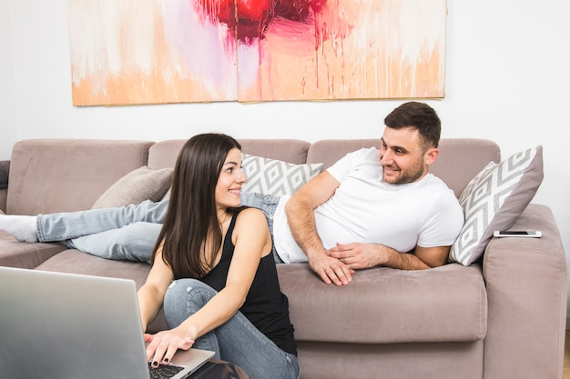 Homem jovem, mentindo, ligado, sofá, olhar, dela, namorada, usando computador portátil
