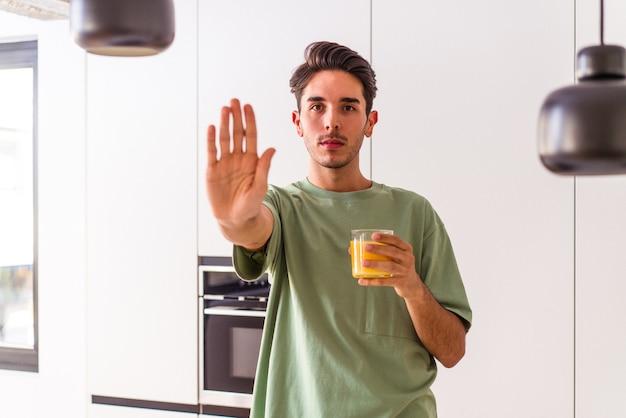 Homem jovem mestiço bebendo suco de laranja em sua cozinha, de pé com a mão estendida, mostrando o sinal de pare, impedindo você.
