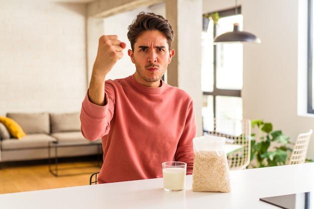 Homem jovem mestiço comendo aveia e leite no café da manhã em sua cozinha, mostrando o punho para a câmera, expressão facial agressiva.