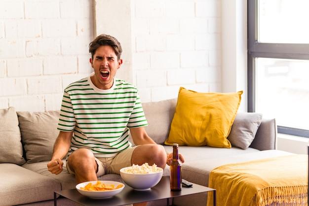 Homem jovem mestiço comendo pipocas, sentado no sofá, gritando com muita raiva e agressividade.