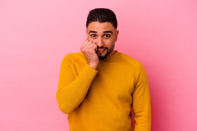 Homem jovem mestiço isolado no fundo rosa, roendo as unhas, nervoso e muito ansioso.