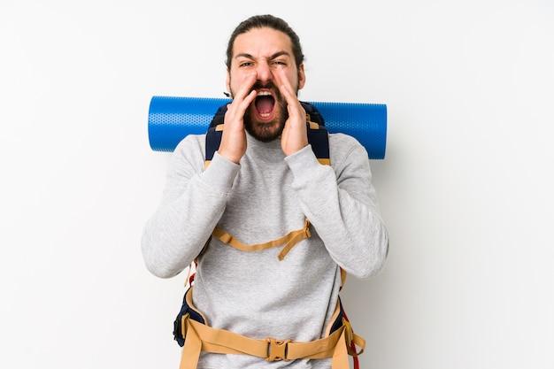 Homem jovem mochileiro em uma parede branca gritando animado para a frente.