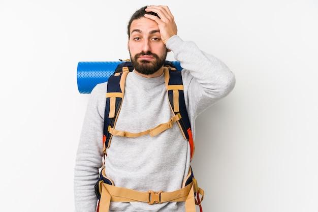 Homem jovem mochileiro isolado em um fundo branco, cansado e com muito sono, mantendo a mão na cabeça.