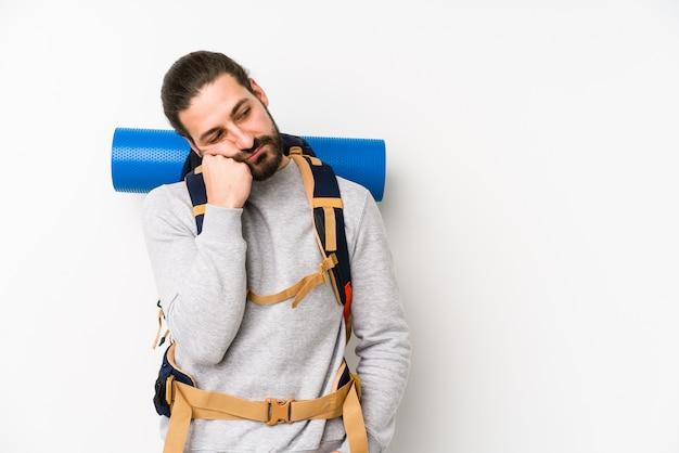 Homem jovem mochileiro isolado no branco que se sente triste e pensativo