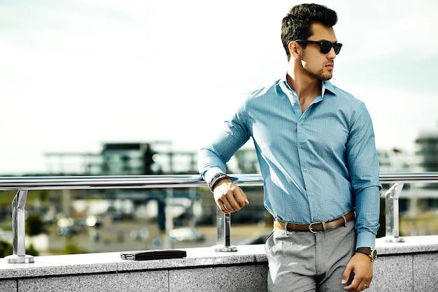Homem jovem modelo bonito empresário em pano casual em óculos de sol na rua