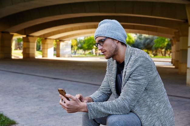 Homem jovem moderno com smartphone debaixo da ponte