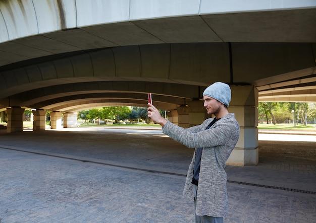 Homem jovem moderno com tablet pc debaixo de uma ponte