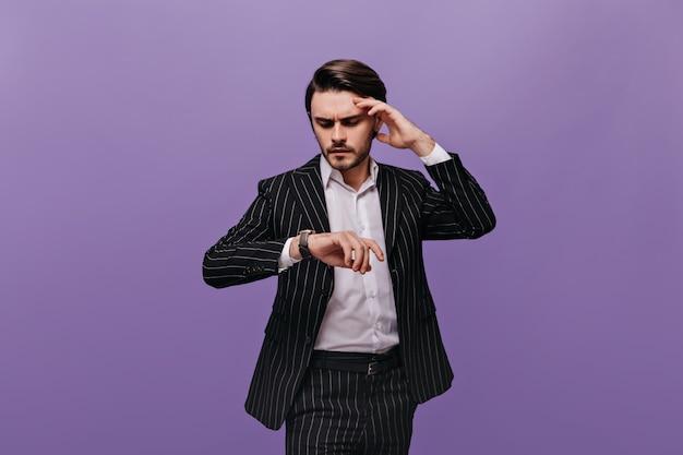 Homem jovem moderno de cabelos castanhos, camisa branca e terno listrado preto, olhando para o relógio na mão e pensando ansiosamente em algo
