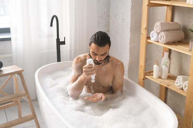 Homem jovem molhado sem camisa usando gel de banho enquanto toma banho com espuma no canto do banheiro