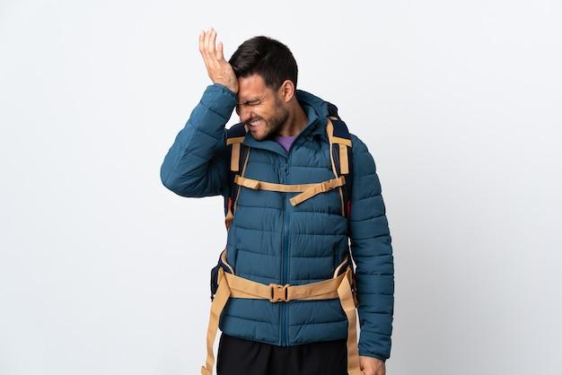 Homem jovem montanhista com uma grande mochila isolada na parede branca, tendo dúvidas com a expressão facial