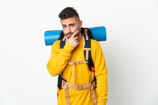 Homem jovem montanhista com uma grande mochila sobre uma parede isolada pensando