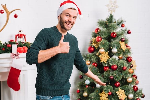 Homem jovem, mostrando, bom, perto, árvore natal