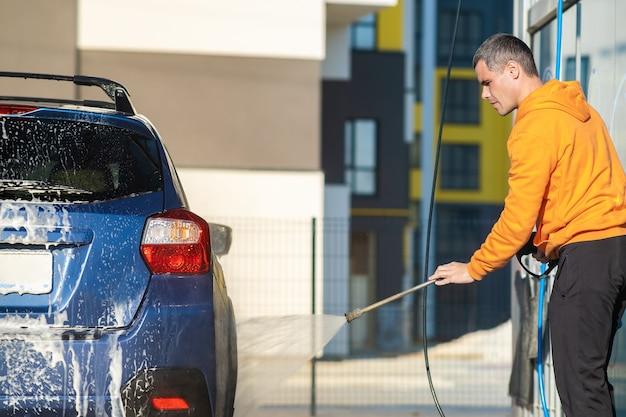 Homem jovem motorista lavando seu carro com jato de água de alta pressão sem contato na lavagem de carros self-service.