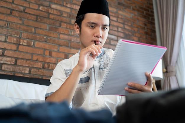 Homem jovem muçulmano segurando uma lista de verificação de papel para bagagem
