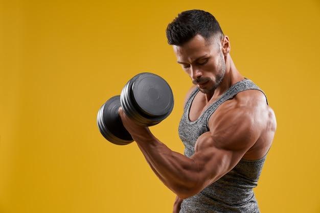 Homem jovem musculoso bombeando bíceps